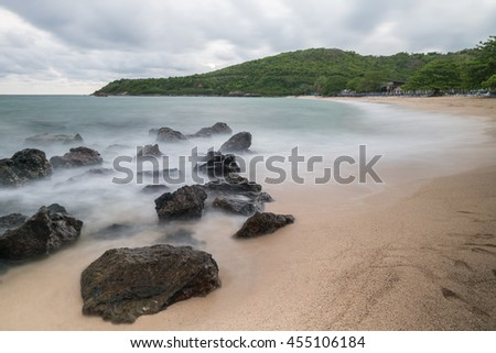 Long exposure of sea and rocks at Nual beach with sandy and cloudy sky in Koh Larn,Pattaya,Chinburi,Thailad - stock photo