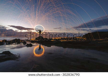 Long exposure of steel wool being spun before dusk on a rocky shoreline on the east coast of Oahu, Hawaii - stock photo