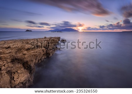 Long exposure of sunset hour on a rocky coast, located in the island of Karpathos, Greece, during summertime.  - stock photo