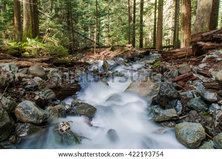 Long exposure of tranquil water flowing downhill on mountain between rocks and green trees - stock photo