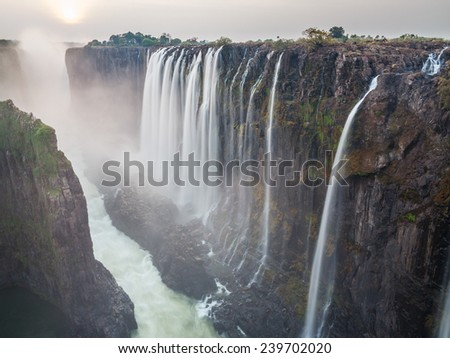 Long exposure of Victoria Falls sunset with zambezi river and red sun, View from Zambia - stock photo