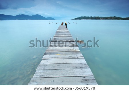 long exposure of wooden jetty at sea facing island with cloud and sky at twilight