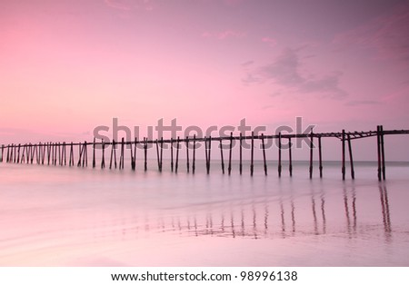 Long exposure old Wood bridge to the sea at sunset - stock photo