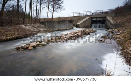 Long exposure photo of dam on river. Landscape with building.