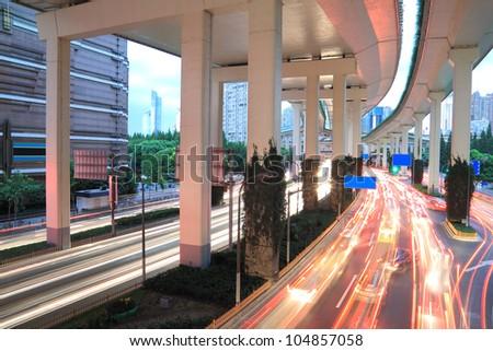 Long exposure photo Shanghai high-speed urban viaduct construction night view car light trails - stock photo