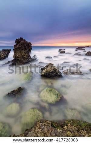Long exposure seascape during blue hour sunset with rocks as foreground. Shot taken Cadiz coast, Spain.