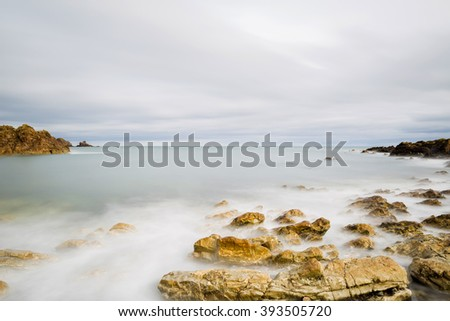 Long exposure seascape with foamy waves splashing against a rocky shore of Coldingham just off Eyemouth in Scottish Boarders - stock photo