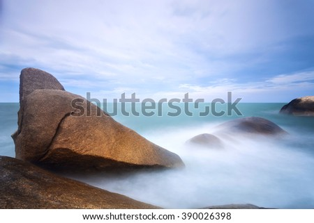 Long exposure seascape with foamy waves splashing against a rocky shore of Samui Island, Thailand - stock photo