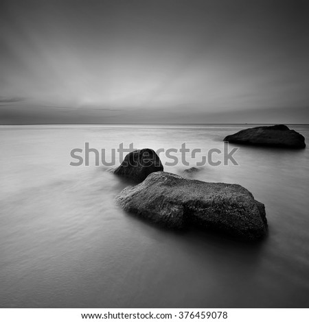 Long exposure seascape with rock foreground in monochrome.