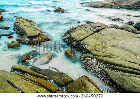 Long Exposure Seascape with running waves on the rocks at the beach - stock photo
