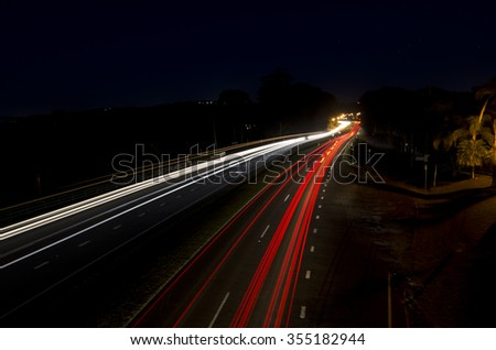 Long exposure shot at night time showing car headlights and tail lights as trails. Some street lights at a distance where the road turns. Complete dark sky.