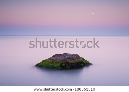 Long exposure shot of a rock in calm waters of the Black Sea in Odessa during a sunset with a moon on the background - stock photo