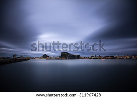 Long exposure shot of Harpa concert hall by the Reykjavik Harbor. shot late at night with dramatic skies overhead - stock photo