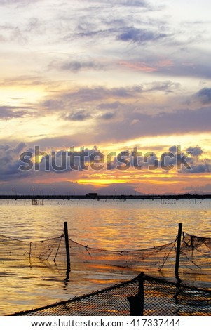 Long exposure shot over the Silhouette image the lake and bridge,mountain,water,boat,fisherman at Songkhla Thailand during sunset.Motion blur, soft focus due to slow shutter speed.