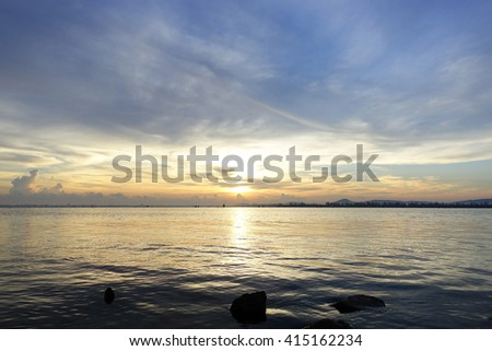 Long exposure shot over the Silhouette image the lake and downtown at Songkhla Thailand during sunset.Motion blur, soft focus due to slow shutter speed.