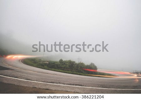 Long exposure showing the blur of passing cars on mountain road on a foggy night. Vehicle driving on curved road in heavy fog. Blur photo styles for foggy and misty.