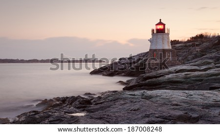 Long exposure sunrise picture of Castle Hill Lighthouse at morning in Newport, Rhode Island, USA on a rocky coastline of the Atlantic ocean. / Castle Hill Lighthouse at Sunrise - stock photo