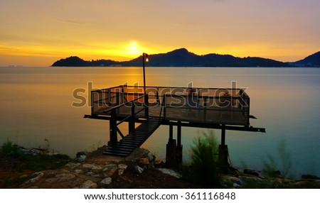 Long Exposure Sunset at Fishing Jetty. Soft Focus and Motion Blur due to Long Exposure Shot - stock photo