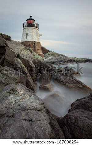 Long exposure sunset picture of Castle Hill Lighthouse at night in Newport, Rhode Island, USA on a rocky coastline of the Atlantic ocean. / Castle Hill Lighthouse at Sunset - stock photo