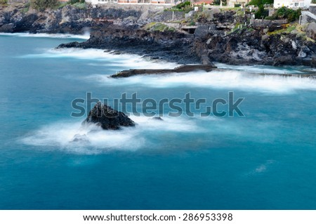 Long exposure view of rocky seashore with deep blue water. Los Gigantes, Tenerife, Canary islands - stock photo