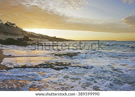 Long exposure winter seascape image of an incoming tide at Porthleven looking towards Loe bar with the soft light of sunrise, Porthleven, Cornwall, England, UK - stock photo