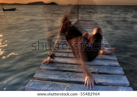Long expusure while the girl's moving on an old jetty in elba island - stock photo