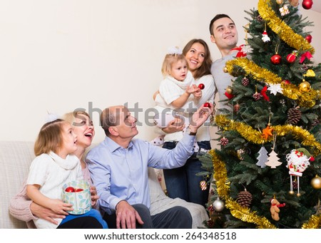 Long family with grand children decorating  christmas fir tree - stock photo