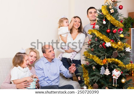 Long family with grand children decorating fir tree - stock photo