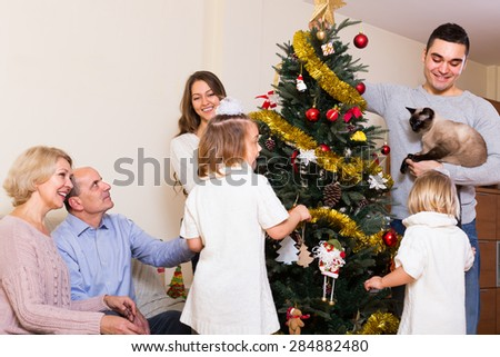 Long family with grand children decorating New Year tree. Focus to young man - stock photo