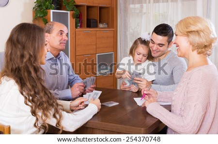 Long family with grand children sitting at table with cards in the room - stock photo