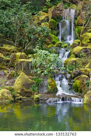 Long Garden Waterfall over moss covered boulders and green vegetation