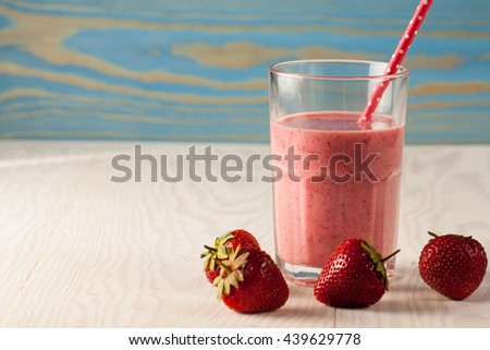 Long glasses of milkshakes with strawberry with ice cream on white and blue background. Shakes and smoothies. Milk shake and cocktail for summer. - stock photo