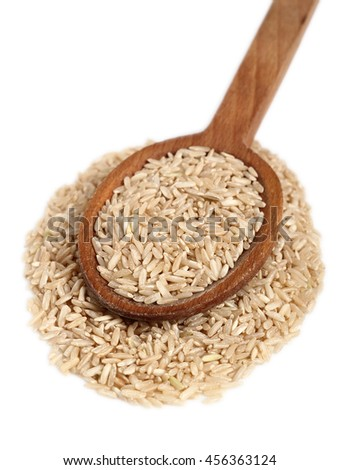 Long grain brown rice on wooden spoon. Isolated on white background.