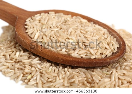 Long grain brown rice on wooden spoon. Isolated on white background. Macro.
