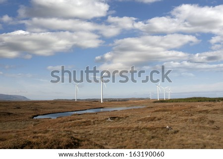 long grass and bogland with wind turbines in the background in Ireland - stock photo