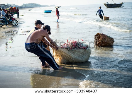 Long Hai, Ba Ria - Vung Tau, Vietnam - 31 May 2015: Fishermen carrying net back home from a long trip at Long Hai, Ba Ria - Vung Tau, Vietnam