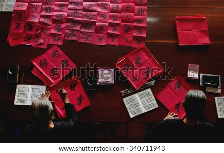 LONG HAI, VIETNAM - JAN 21, 2014: Two unknown old men are writing Han Nom words - a kind of letters that used to be famous during feudalism. They are given to visitors to wish they luck in new year.