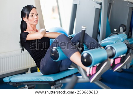 Long hail brunette doing crunch on bench. - stock photo