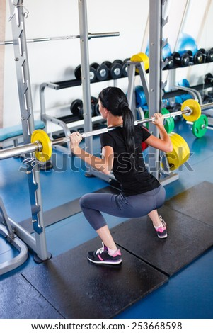Long hail girl doing squats with a barbell. - stock photo