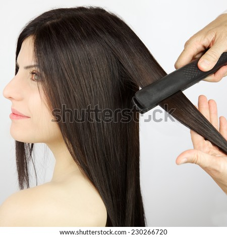 Long hair being straightened with iron by stylist - stock photo