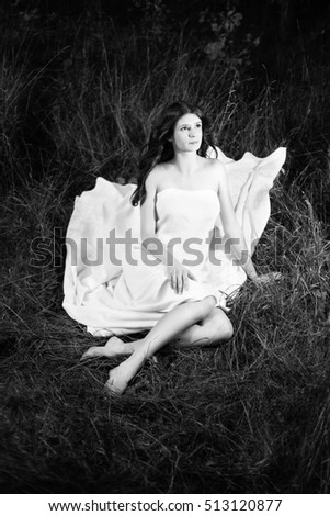 Long hair girl in a white cloth on grass.