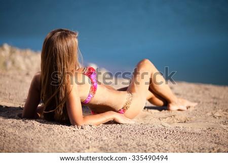 Long hair girl in bikini on beach. - stock photo