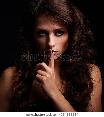 Long hair girl showing secret sign and looking. Closeup portrait on black - stock photo