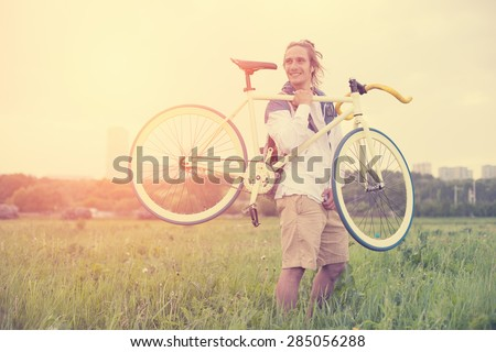 Long hair man holding bicycle in green field at sunset (intentional sun glare and vintage color)