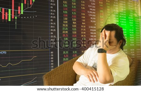 Long hair stress man sitting in chair hold head with hand with Stock market chart and data board as background/Stock market chart with stress man  - stock photo