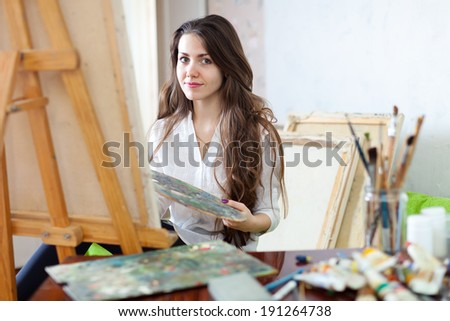 Long-haired  artist paints picture on canvas with oil paints in  workshop - stock photo