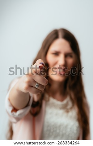 long-haired beautiful brunette girl shoots a finger, isolated on a white background