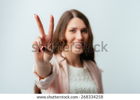 long-haired beautiful brunette girl showing two fingers, positive or peace gesture, on white - stock photo