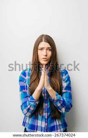 long-haired beautiful girl asks for forgiveness, isolated on white background - stock photo