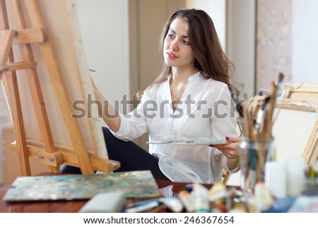 Long-haired beautiful woman paints on canvas in workshop - stock photo